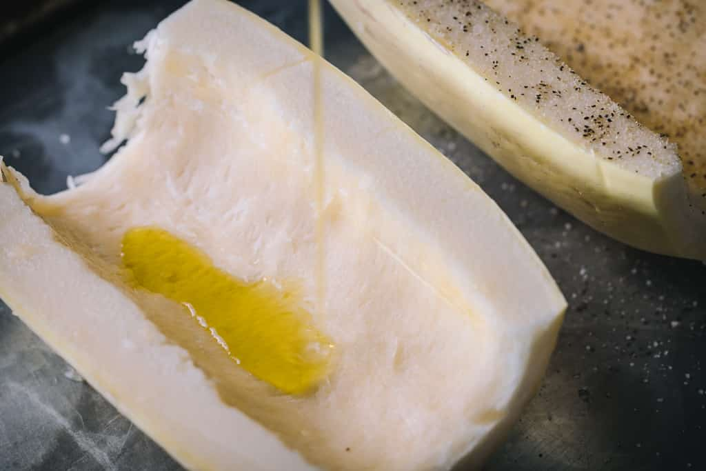 Spaghetti squash half being drizzled with olive oil.