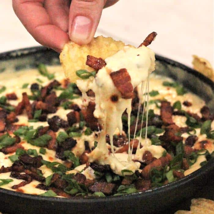 skillet bacon queso dip on a potato chip over a skillet full of bacon queso dip