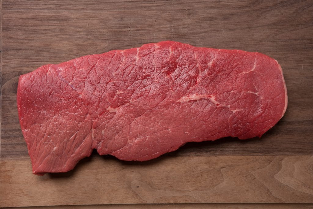 Uncooked top round roast sitting on a wood cutting board