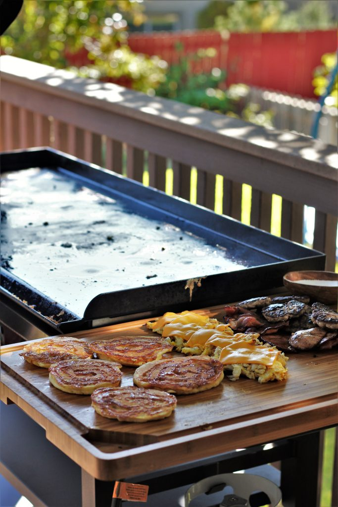 Cheese topped scrambled eggs, pancakes, and sausages arranged on a wood cutting board next to a flat top grill.
