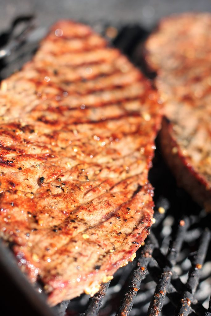 London broil slices grilling on charcoal grill grates.