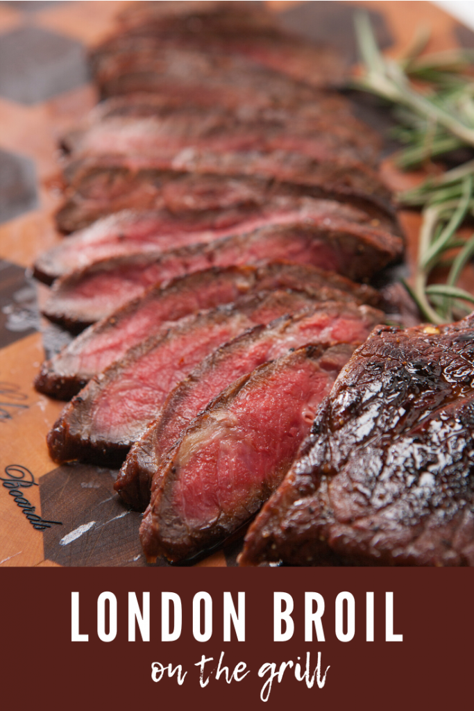 Medium sliced london broil on a wood cutting board with a sprig of rosemary.