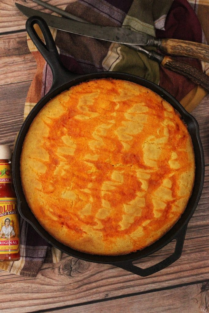 Finished Cholula Swirled Cornbread on top of Spicy Pulled Pork in a cast iron pan. Overhead shot with serving utensils, decorative dish towel, and a bottle of cholula hot sauce on the side.