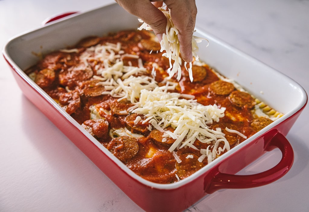 Cheese being sprinkled on top of a rectangular baking dish of smoked Italian sausage lasagna.