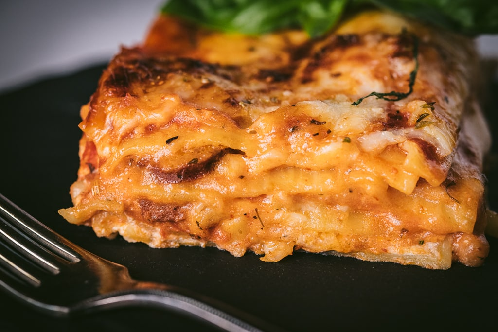 A slice of smoked Italian sausage lasagna on a black plate with a metal fork in the foreground.