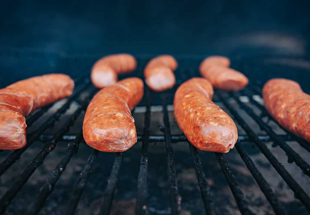 Italian sausage links liked up on the grill grates of a smoker.