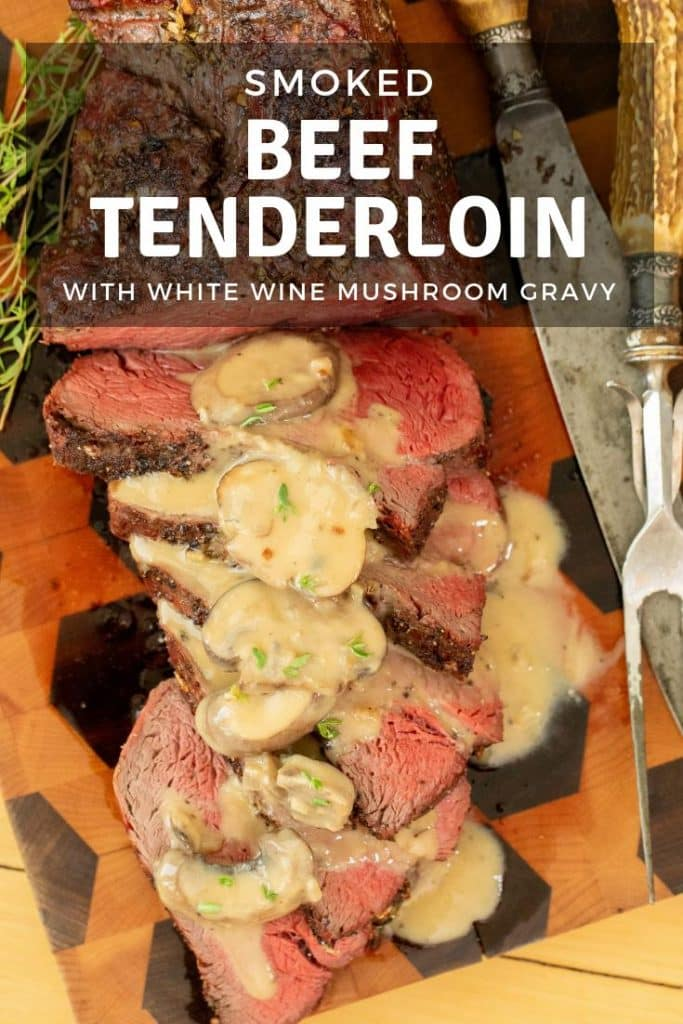 smoked beef tenderloin topped with white wine mushroom gravy on a wooden cutting board.