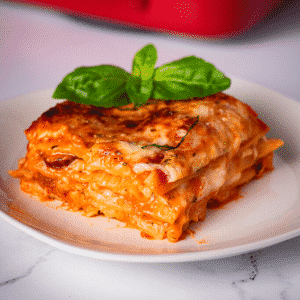 One slice of smoked Italian sausage lasagna on a white plate.
