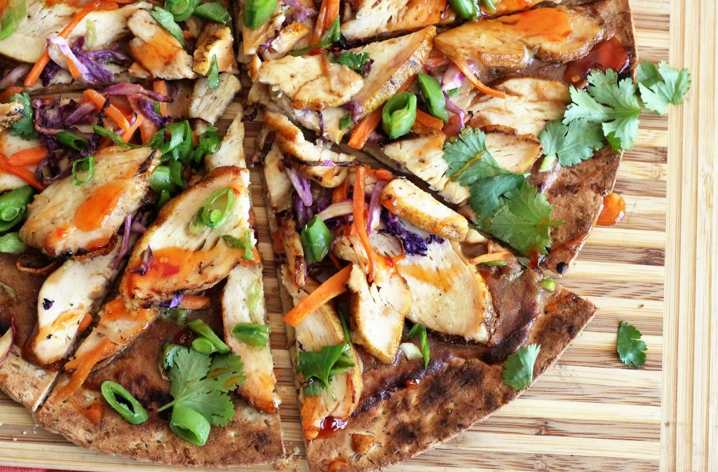Thai Grilled Chicken Pizza with Curry Grilled Chicken and Thai Peanut Sauce on a cutting board.