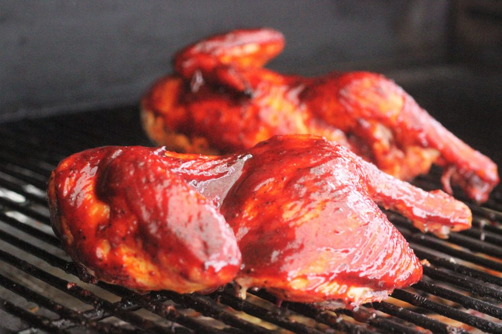 Sauced chicken on a grill grate inside the grill.