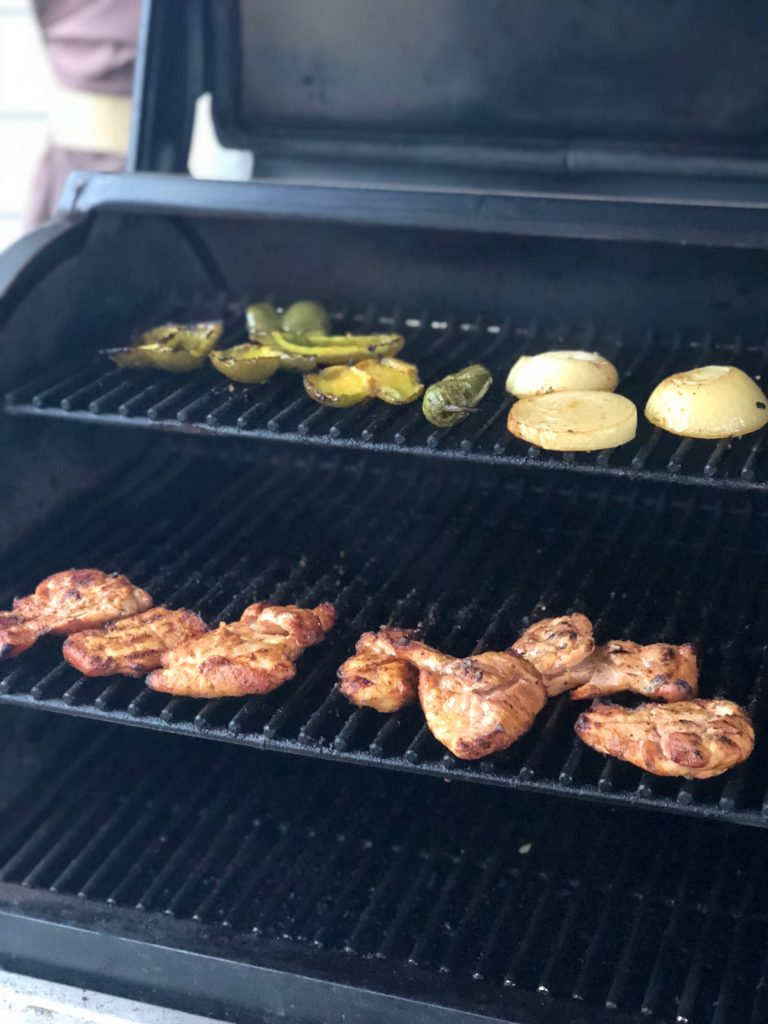Chicken thighs on the grill with some jalapenos and onions.