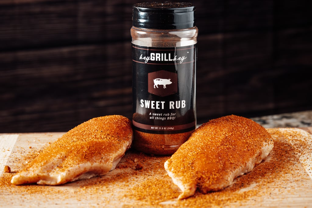 Hey Grill Hey Sweet Rub sprinkled on two uncooked chicken breasts with a bottle of Sweet Rub in the background.