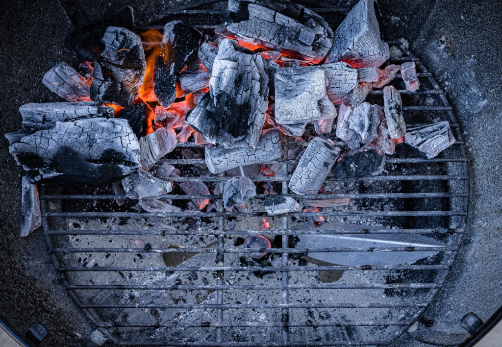 Overhead view of a charcoal grill with hot briquettes on the top half of the grill.