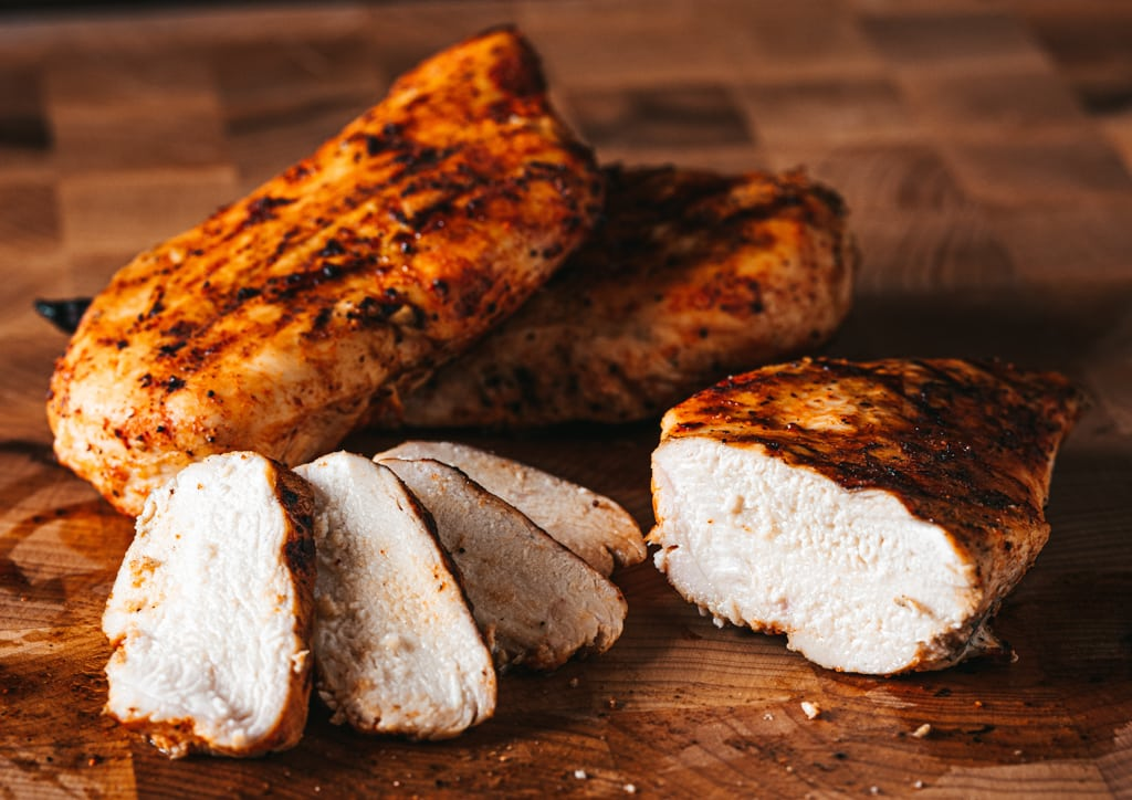 Sliced grilled chicken breast on a wooden cutting board with two whole grilled chicken breasts in the background.