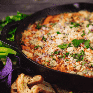 Buffalo chicken dip in a cast iron skillet surrounded by crostini and fresh veggies.