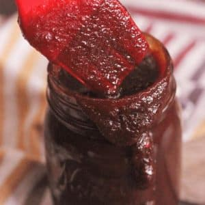 Red basting brush covered in Kansas city style bbq sauce resting on the edge of a glass mason jar full of the same sauce.