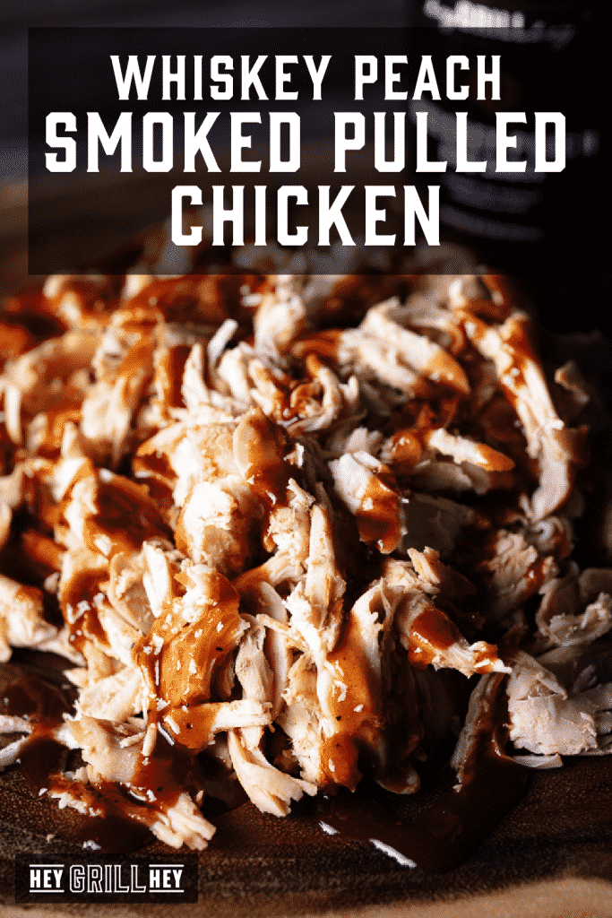 Shredded smoked chicken on a wooden cutting board covered with whiskey peach BBQ sauce with text overlay - Whiskey Peach Smoked Pulled Chicken.