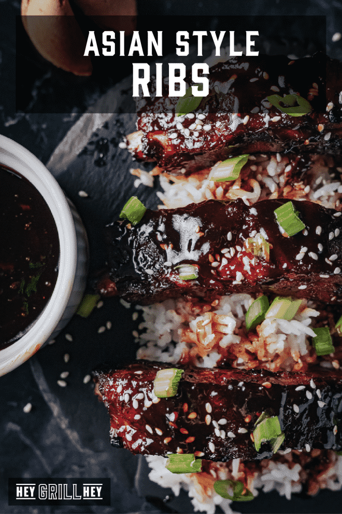Smoked Asian style ribs garnished with sesame seeds over a bed of rice with text overlay - Asian Style Ribs.