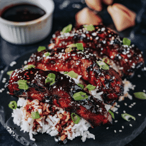 Smoked Asian style ribs garnished with sesame seeds over a bed of rice.