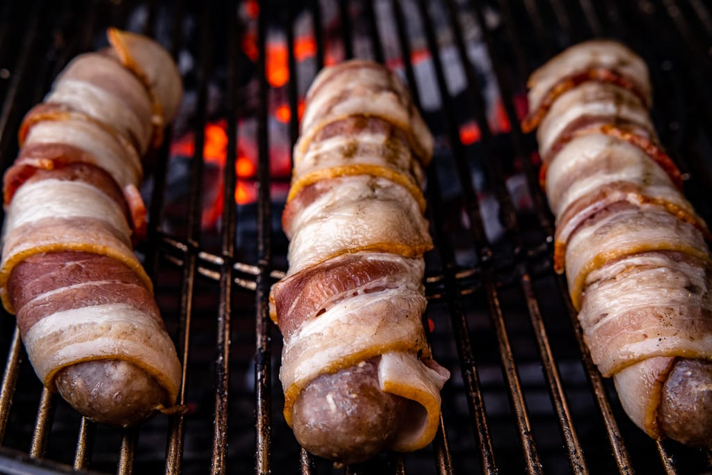 Three bacon wrapped brats on grill grates with hot charcoals underneath.