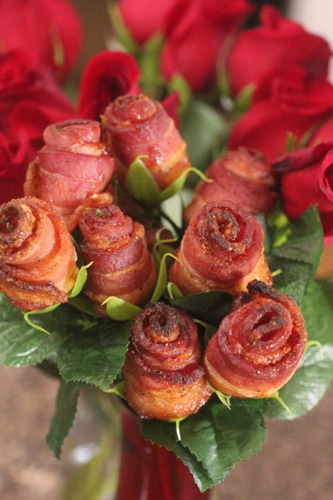 bacon roses in a red glass vase.