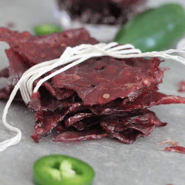 Stack of Dr. Pepper jalapeno beef jerky wrapped in white twine on a gray table surrounded by fresh jalapenos.