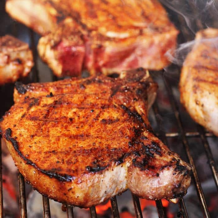 grilled pork chops on a grill grate over hot coals.
