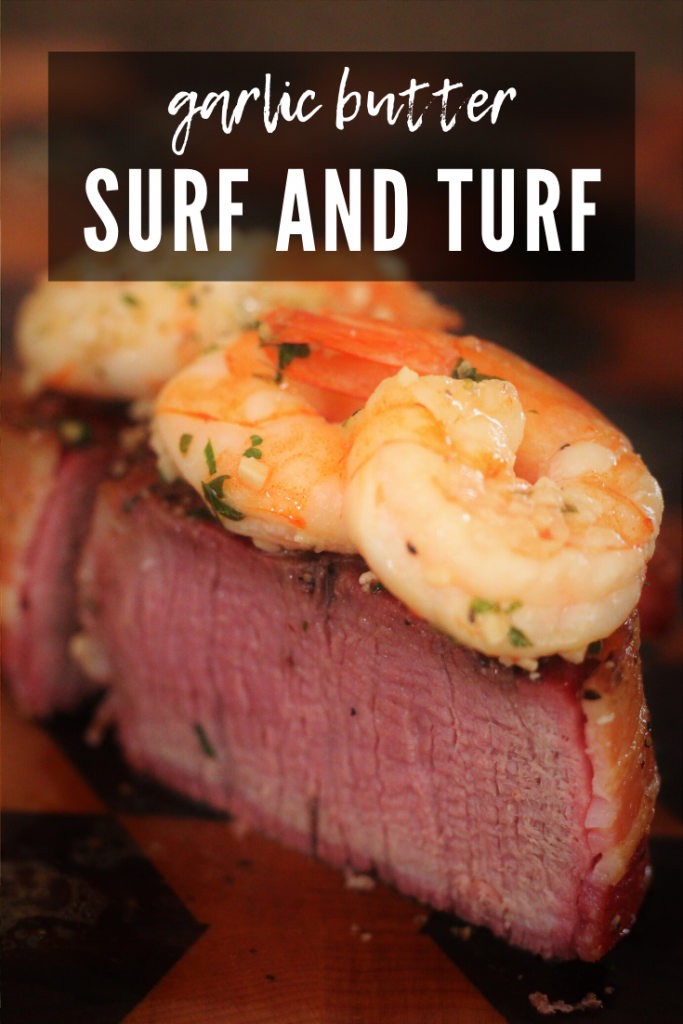 surf and turf on a wooden cutting board (grilled shrimp on top of filet mignon).