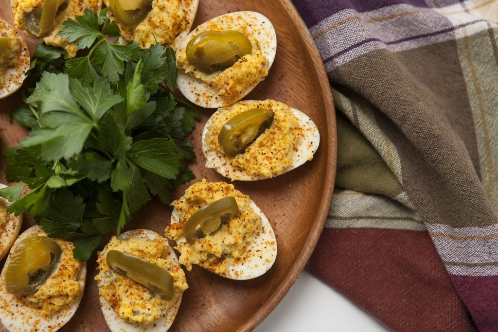 Smoked Deviled eggs arranged in a circle on a wooden plate.