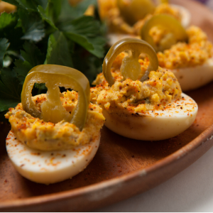 Smoked deviled eggs each topped with a pickled jalapeno arranged on a wooden serving plate.