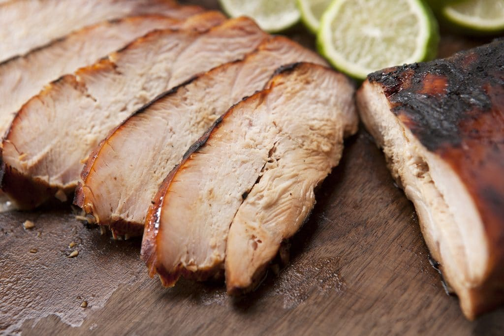 Sliced smoked turkey breast on a wood cutting board with sliced lemons and limes.