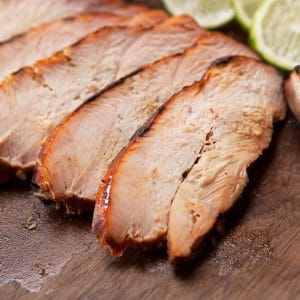 Smoked turkey breast sliced and served on a wooden cutting board.