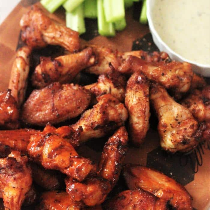 smoked then fried chicken wings on a wooden board next to a white bowl of dipping sauce and cut celery stalks