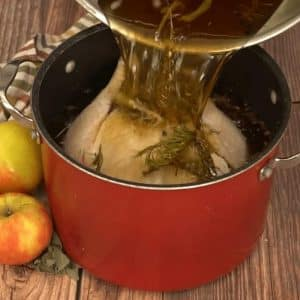 Apple spice turkey brine being poured over a whole uncooked turkey in a large stock pot.