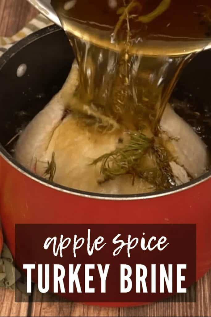 Pouring turkey brine into a large stock pot with a raw turkey in it.