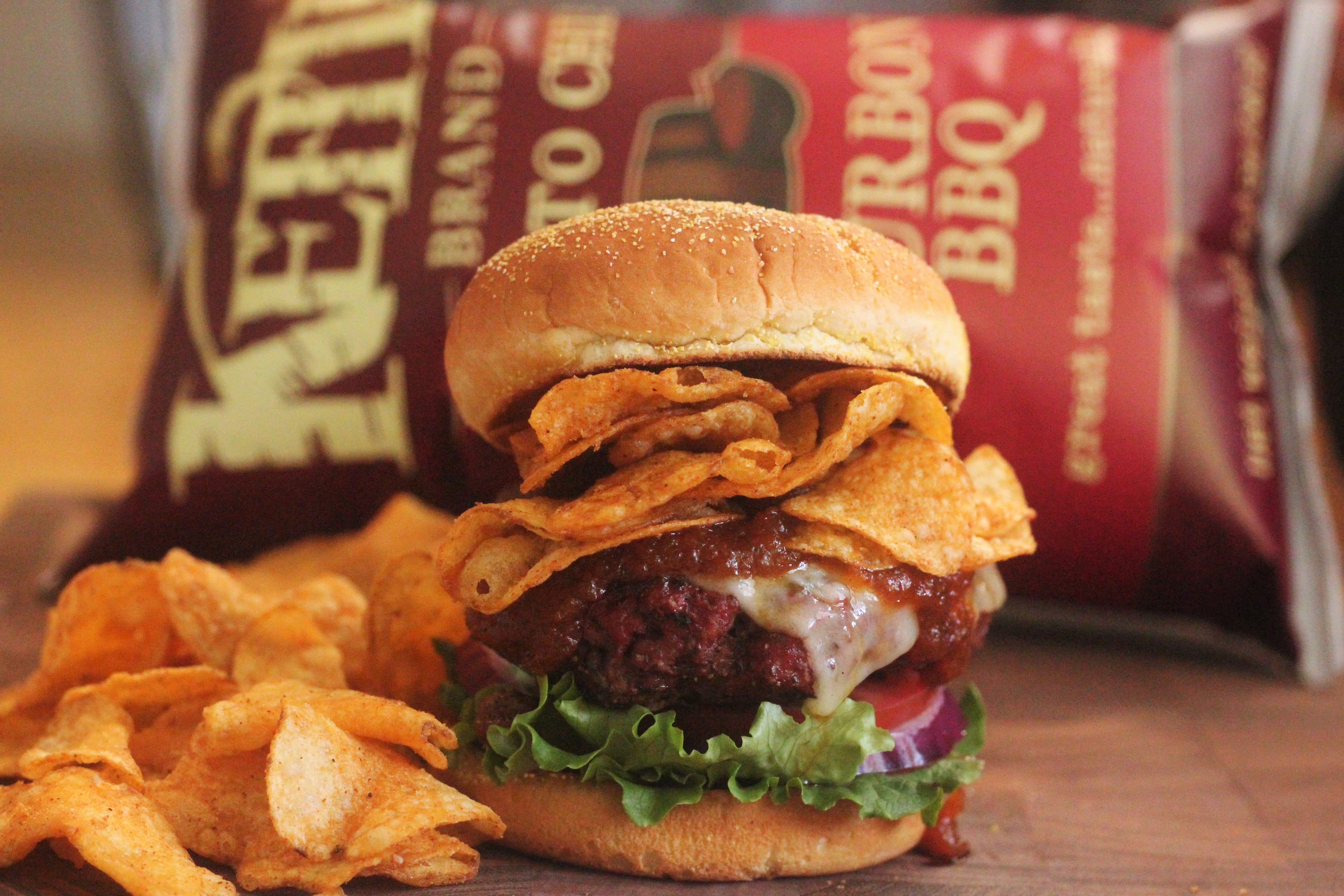 burger and chips on a wooden table.