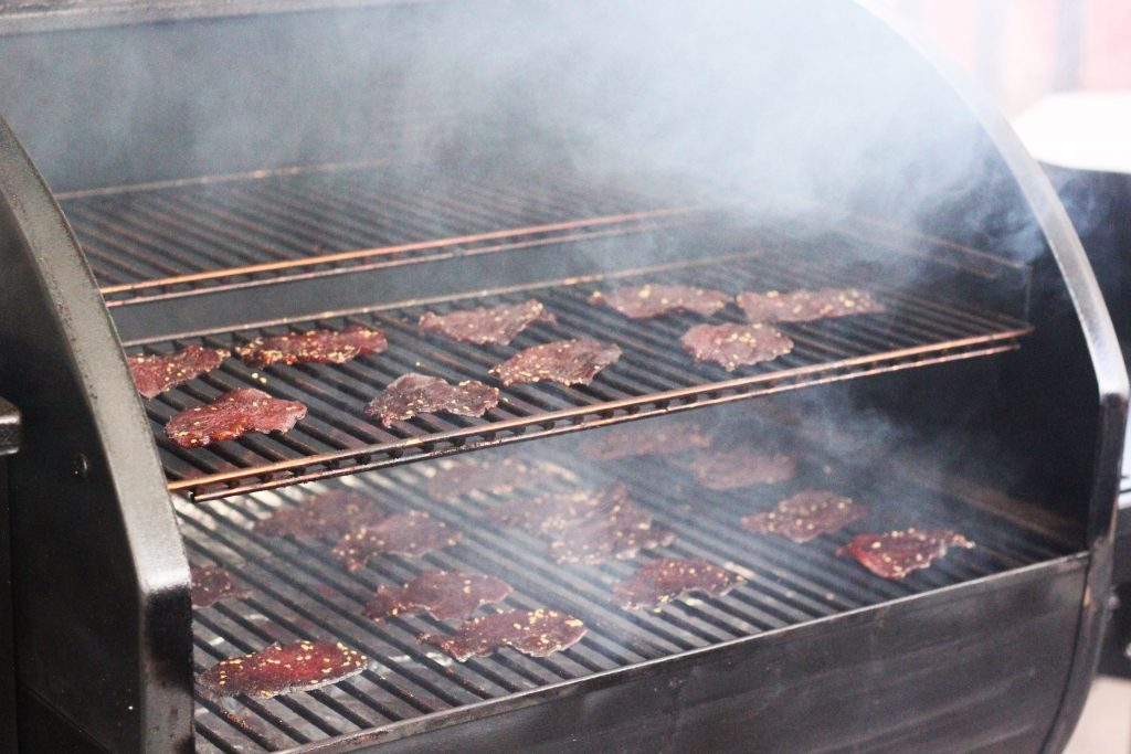 Sliced and marinated teriyaki beef jerky spread out on a smoker with smoke rising up from the bottom of the smoker.