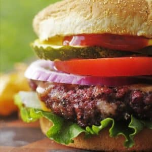 Smoked hamburger topped with pickle, tomato, onion, and lettuce on sesame seed bun.