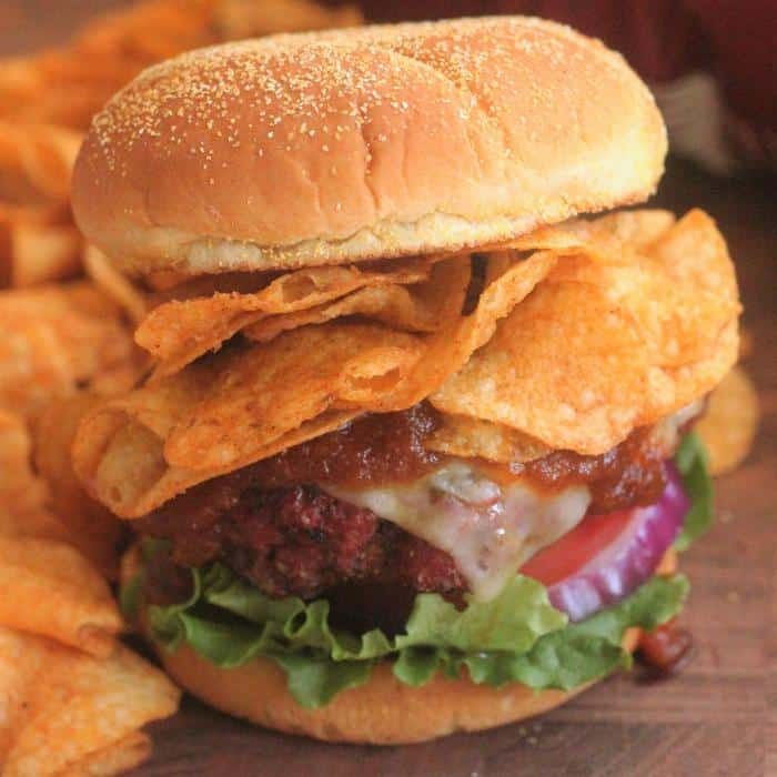 Hamburger on a bun with lettuce, onion, sauce, and potato chips