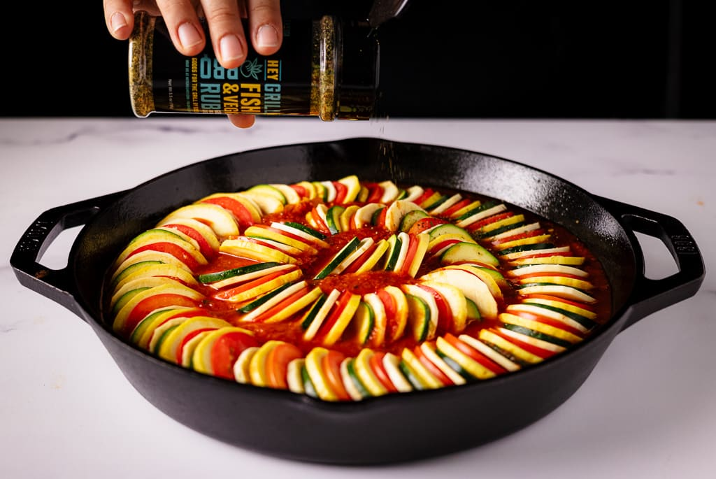Fish and Veggie Rub being sprinkled on top of arranged ratatouille in a cast iron skillet.