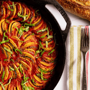 Grilled ratatouille in a cast iron skillet next to a baguette of bread.