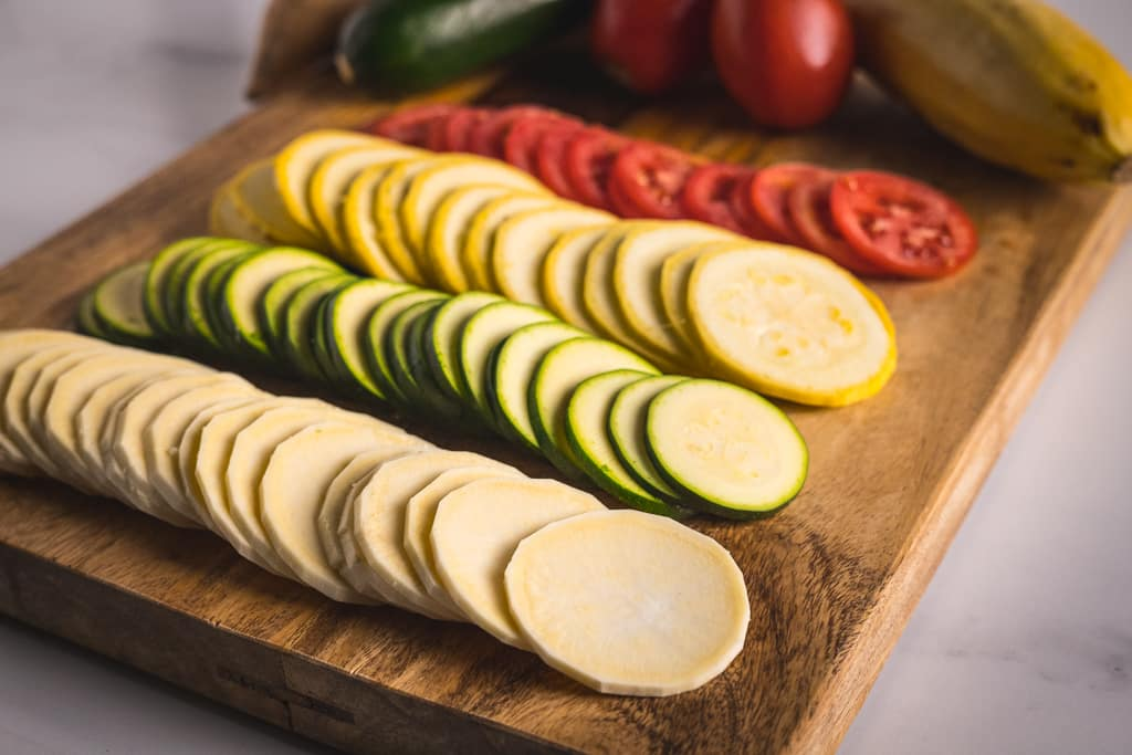 Four rows of sliced vegetables for ratatouille on a wooden cutting board.