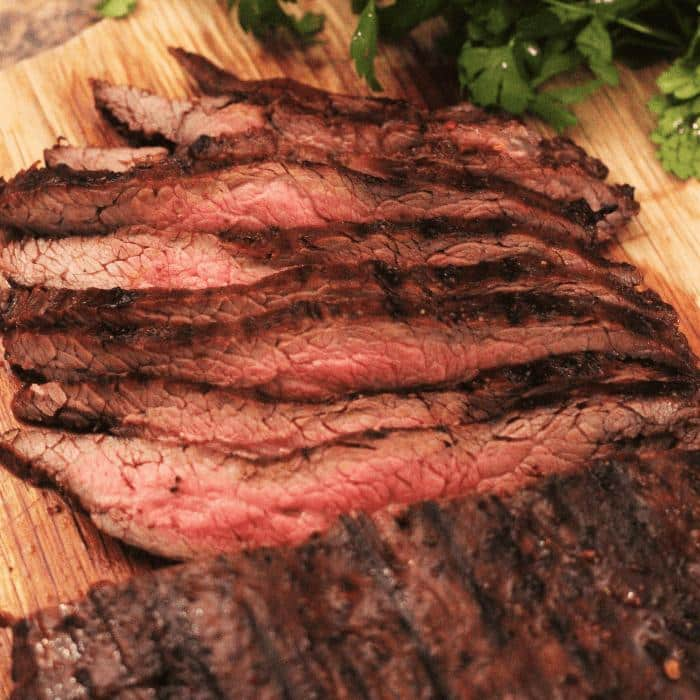 sliced marinated and grilled flank steak on a wooden cutting board next to fresh herbs