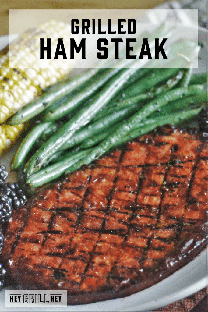 Grilled ham steak on a plate next to green beans and corn on the cob with text overlay - Grilled Ham Steak.