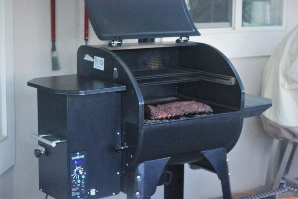 smoked ribs sitting on the grates of a pellet smoker with the lid open.