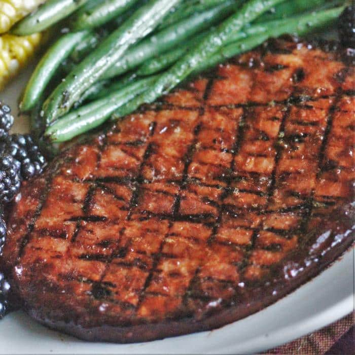 grilled ham steak on a white plate next to blackberries and string beans