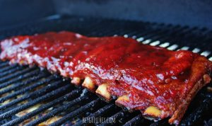 sauced rack of ribs on the grates of a pellet smoker.