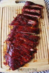 sauced and sliced smoked ribs on a wood cutting board.