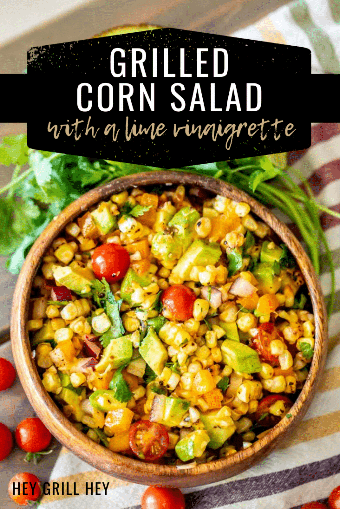 A wooden bowl sitting on a striped kitchen cloth surrounded by cherry tomatoes and cilantro. The bowl is full of grilled corn salad with corn, cherry tomatoes, and avocado slices.