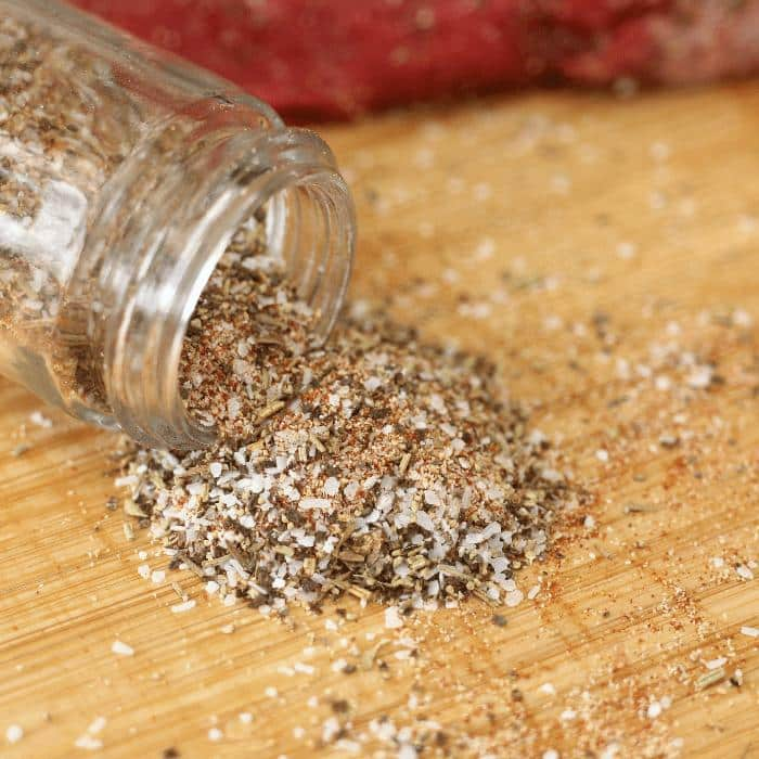 Homemade steak seasoning pouring out of an open glass spice jar onto a wooden cutting board.